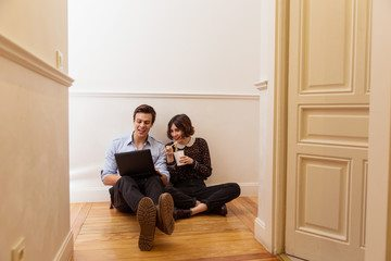Couple using laptop to look at companies to help with moving abroad