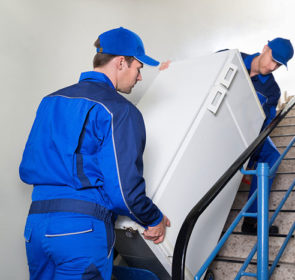 Movers carrying a fridge up a set of stairs