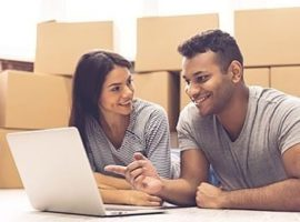 Couple using laptop to look at moving house quotes