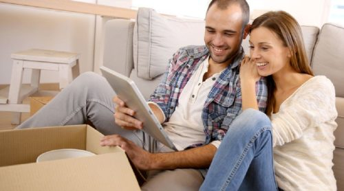 Couple using tablet to compare furniture removal prices